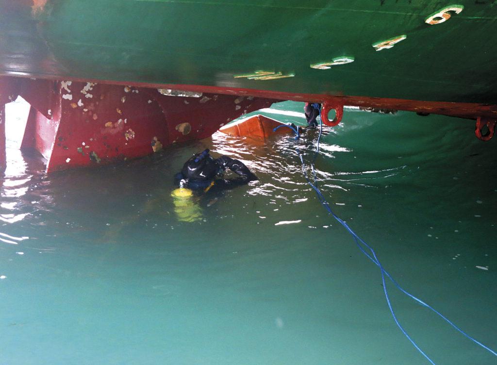 водолаз проводит осмотр судна